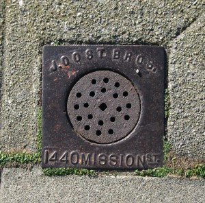 Joost Bros branded sewer vent, minted before the 1906 Quake with the old store location, but installed on this sidewalk on Gennessee Street in the 1920s.
