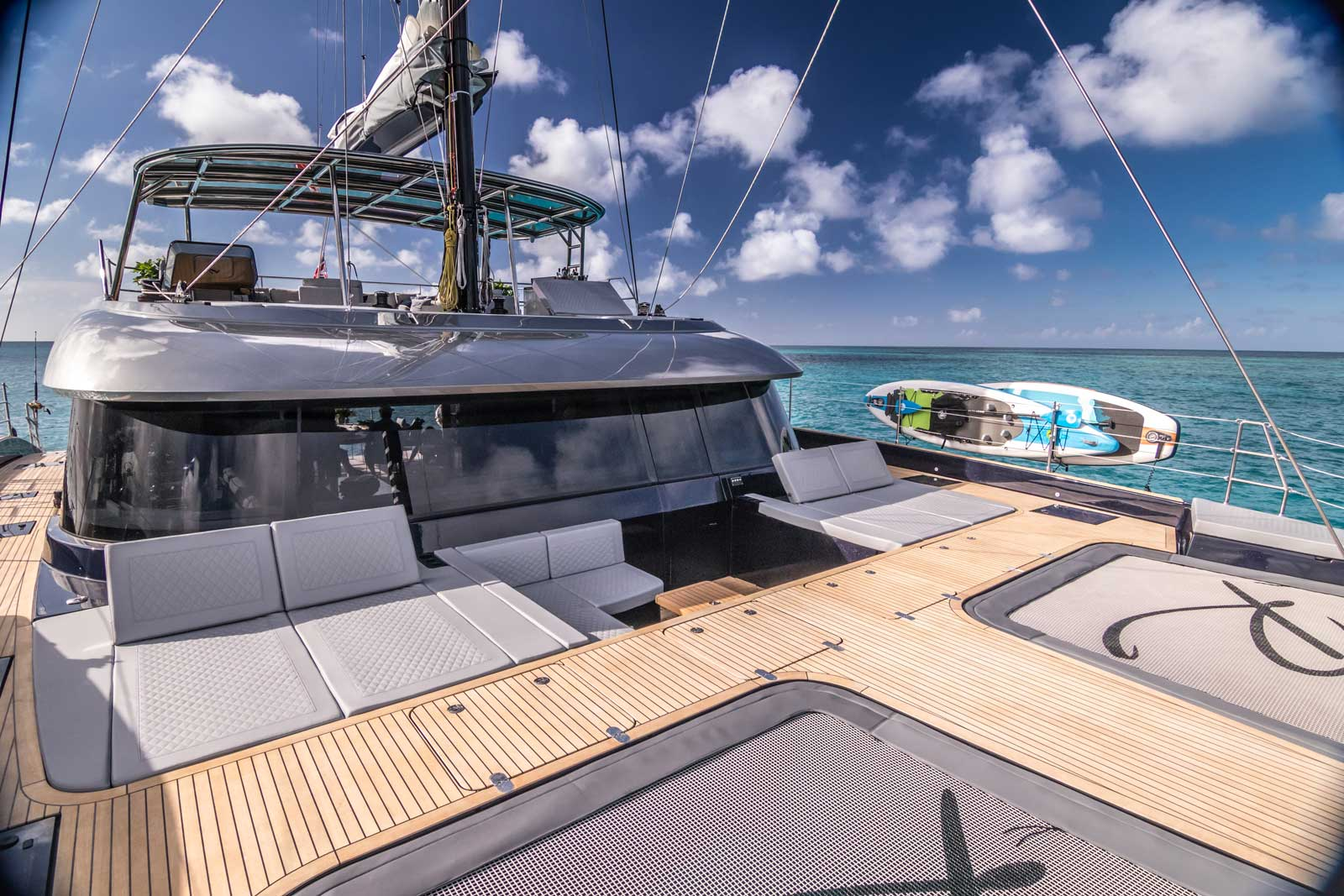 Bow terrace of an electric sailing catamaran Sunreef 60 with oversized sunpads and two trampolines with a yacht's logotype.