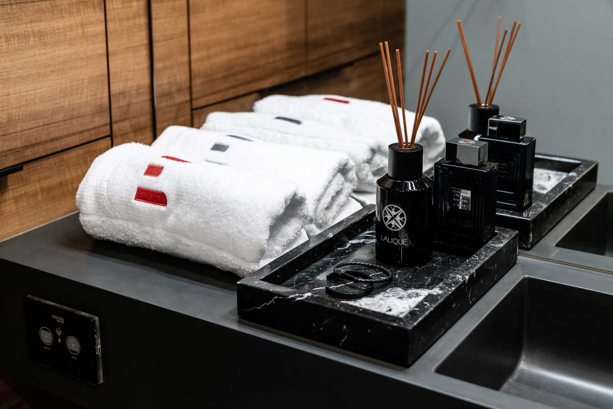 """Home perfumes and the branded Sunreef 60 """"E"""" towels on the bathroom counter."""