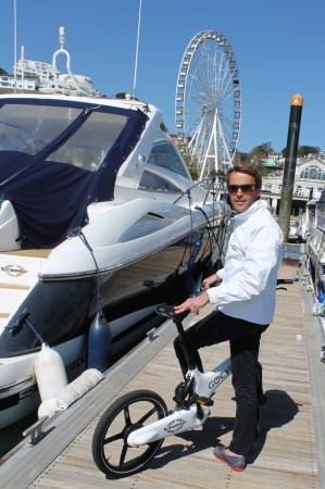 Tom Wills tests out the bike alongside a Sunseeker in Torquay marina