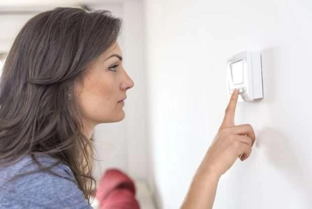 Woman checking thermostat – Blank thermostat screen - Fort Myers - Sunset Air & Home Services
