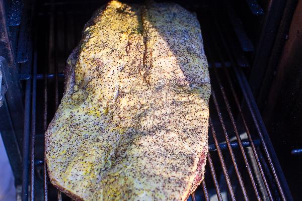 uncooked seasoned brisket on rack in smoker