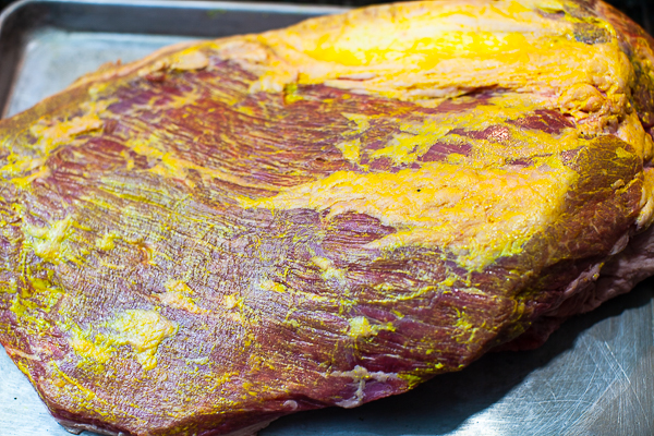 underside of uncooked brisket smoothered with layer of yellow mustard