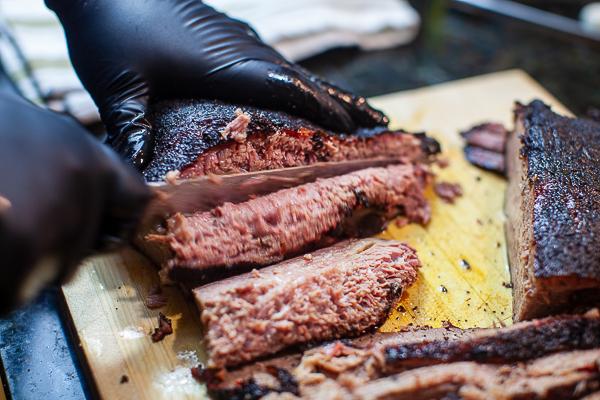 black gloved hands slicing brisket on wooden cutting board