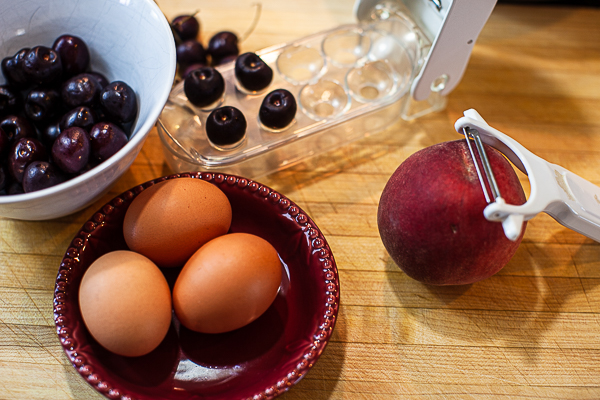 small bowl of cherries, cherry pitter, 3 brown eggs, peach with peeler on cutting board