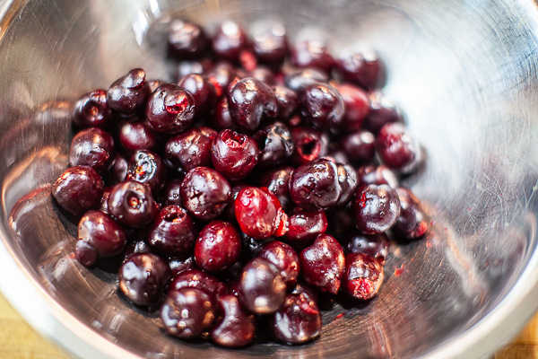 silver mixing bowl containing pitted cherries