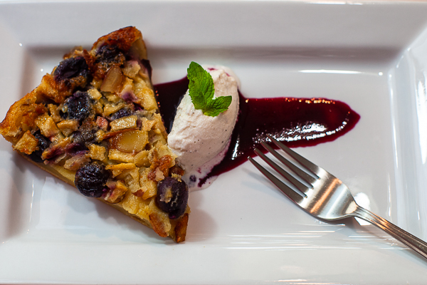 white plate with wedge of clafoutis, drizzle of cherry sauce, vanilla ice cream and mint,fork on side