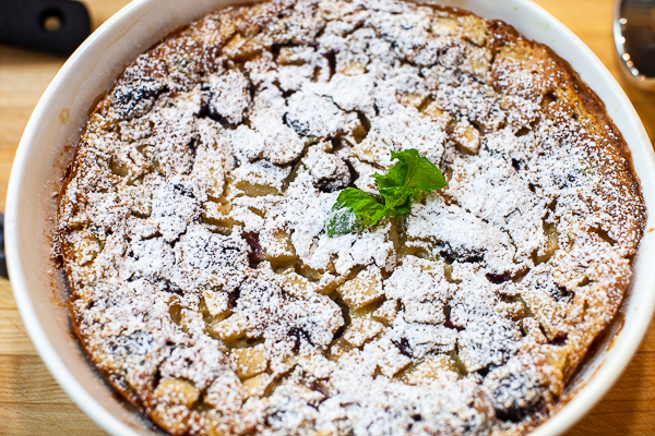 dish containing cooked clafoutis dusted with powdered sugar, mint sprig