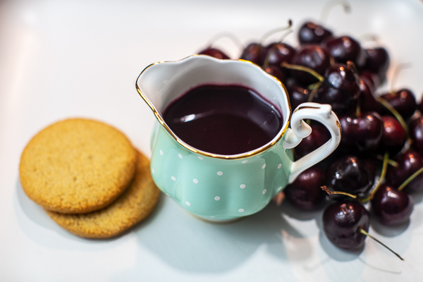 turquoise creamer containing cherry syrup next to cherries and shortbread cookies