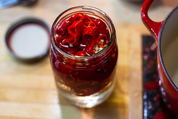 glass jar filled with chiles and vinegar solution