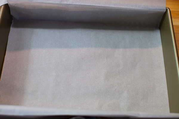 baking pan containing folded parchment over length edge