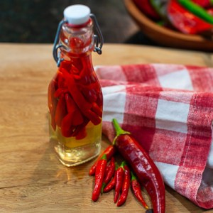 glass jar of red chiles on cutting board next to fresh chile peppers