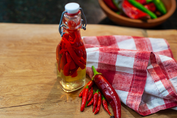 small jar of childs and vinegar solution on cutting board next to fresh chiles