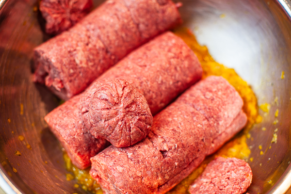 rolls of ground beef added to onion, turmeric, saffron water, salt and pepper mixture in bowl