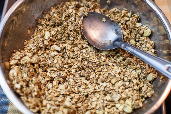 granola mixture in mixing bowl with water added and spoon used to mix