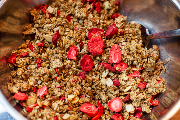 metal mixing bowl containing granola and dried strawberries, mixed with spoon