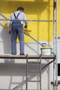 Painter working from a platform on rented scaffolding