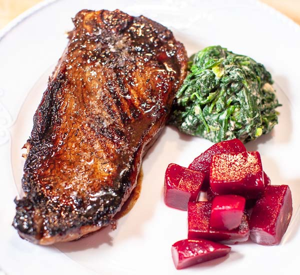 Broiled New York Strip Steak with creamed spinach and pickled beets