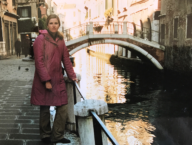 Kate standing in pink coat in Venice