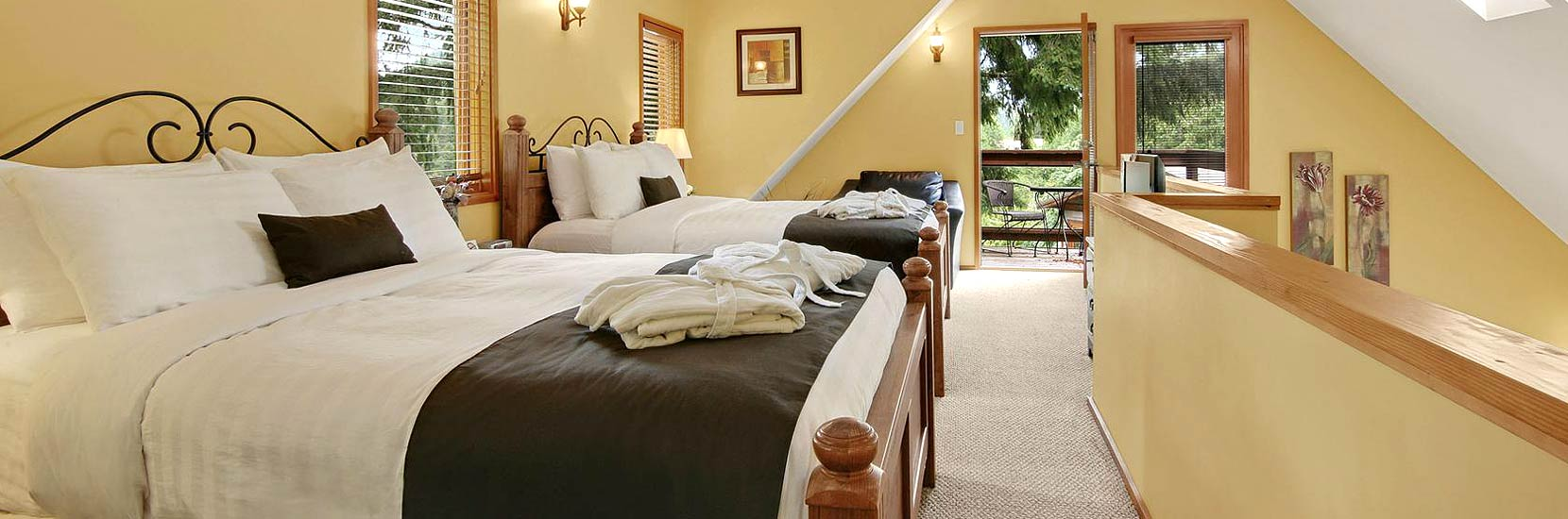 The Executive Cottage upstairs bedroom features 2 queen beds, private bath, LCD TV and balcony
