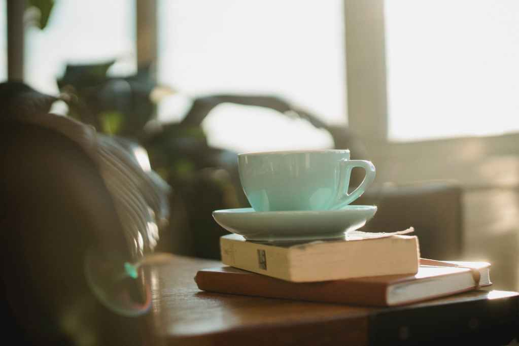 cup with plate and book with notebook on table
