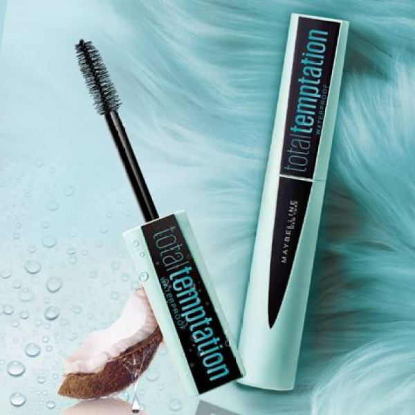 maybelline total temptation mascara with coconut piece on a blue background