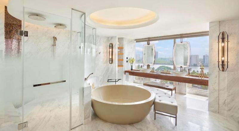 presidential suite bathroom at grand hyatt kochi with round bathtub with chaise lounge chair and separate shower cubicles in white marble