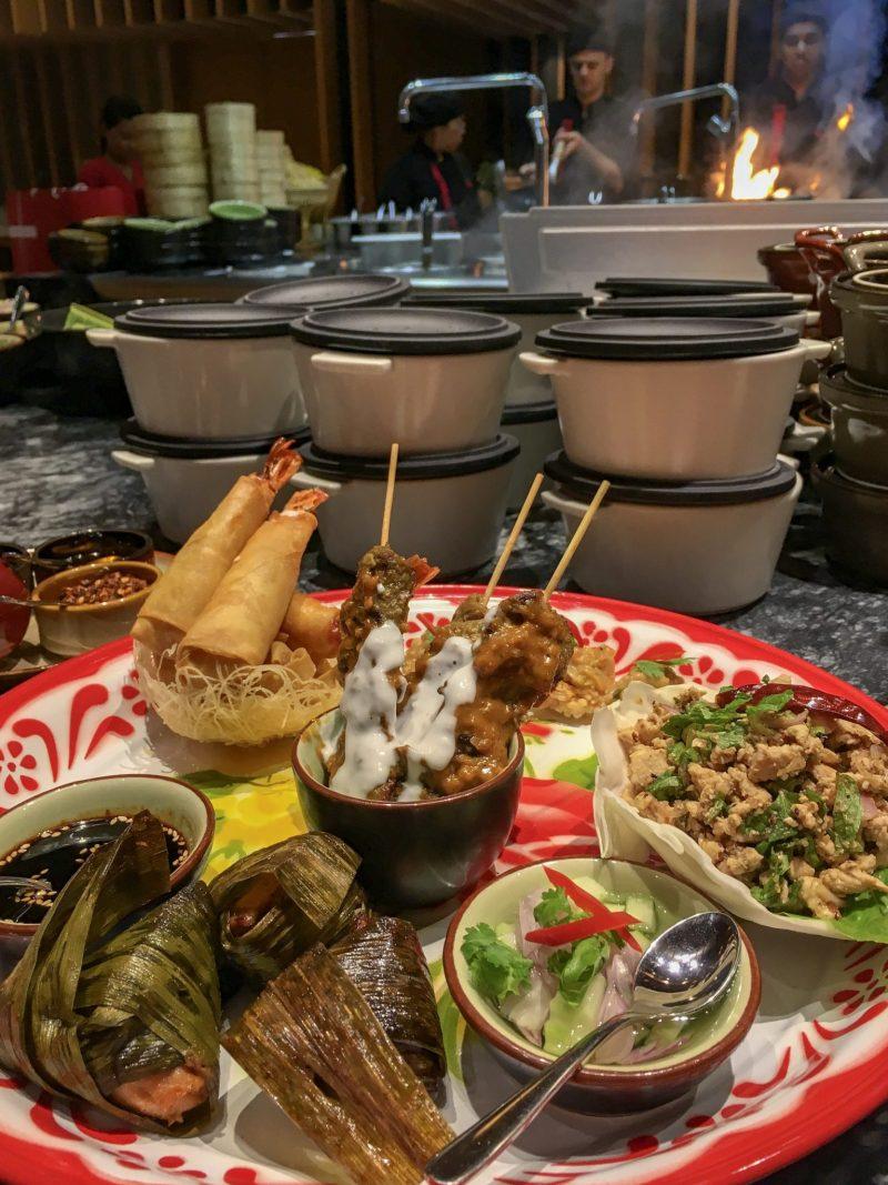 Thai food appetizer platter with pandan chicken, prawn springrolls, chicken laab, chicken satay skewers and sauces