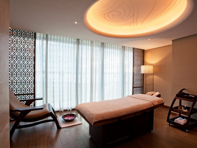 inside Santata spa treatment room with bed and a chair with footbath