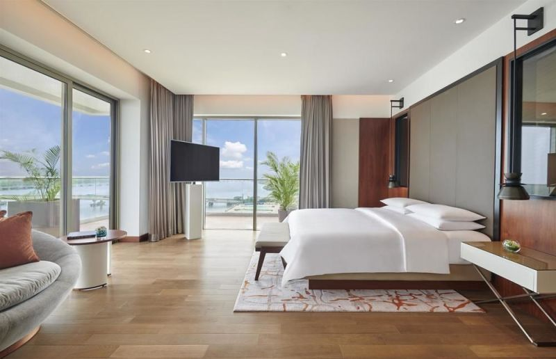 terrace suite with floor to ceiling windows on two sides and king bed in grand hyatt kochi suite