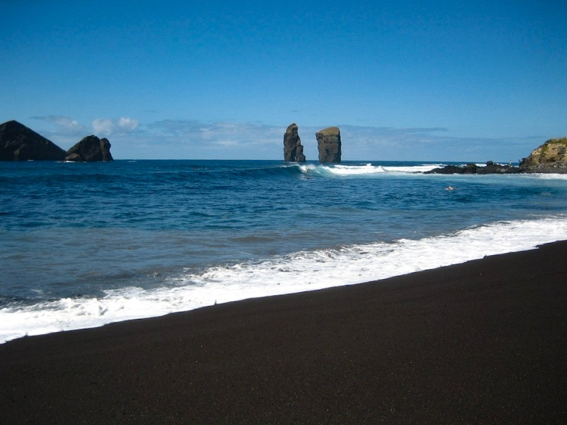 two lava rock formations in the background of black sand Mosteiros beach