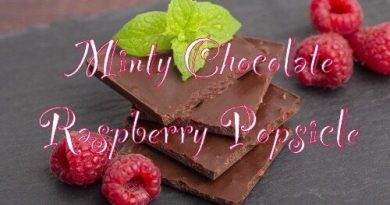 dark chocolate with mint leaves and fresh raspberries on a stone board