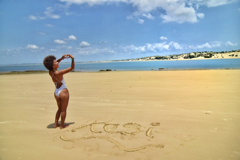 woman with white swimwuit and heart hand sign on shela beach in lamu island
