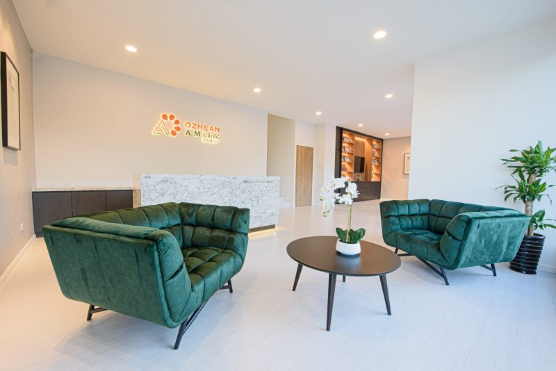 reception area of ozhean clinic bangsar branch with velvet green chairs and white interior