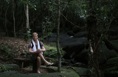 Dan, sitting in a school boy pose on a seat in the forest