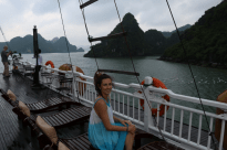 Tegan sitting on a sun lounge on the roof top of the boat in Ha Long bay, a cloudy day but still magnificent, limestone mountains in the background.