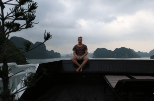 Dan sitting on the back of the boat, limestone mountains dotted behind him
