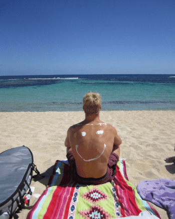 Dan sitting on the sand with a smiley face on his back in sunscreen overlooking the clear blue sea