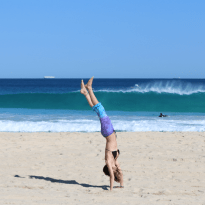 Tegan upside down, handstand in front of a breaking wave, blue sky and sea