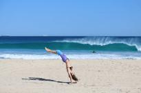 Tegan in handstand falling backwards, wave breaking behind her