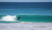 blue ocean, turquoise clear face offshore wind blowing the white wash behind the wave, Dan pulling in to the barrel