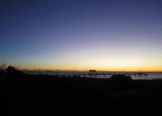 Sunset over the jetty at Jurien Bay, yellow along the horizon and shades of blue getting darker toward the top