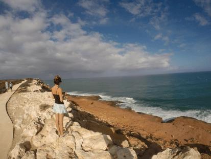Tegan overlooking the ocean at Kalbarri, red dirt/dust