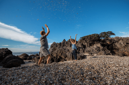 Dan and Tegan arms raised, action shots throwing shells over each other. Shells covering the beach instead of sand