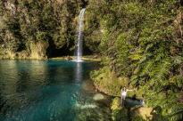 Sun streaming through onto the pool, turquoise clear water, Tegan walking around the rocks below