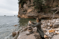 Tegan stacking rocks into a Zen rock stack, ocean in the background, rocky beach below