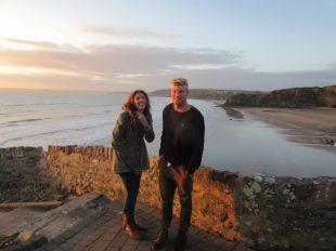Tegan laughing at something Dan has said, in front of the ocean