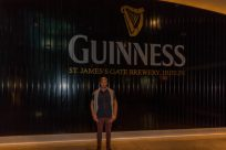 Dan standing in front of the Guiness factory, guiness written on the wall in white, against a black wall