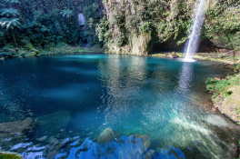 Turquoise blue, dark blue patches in a lake, waterfall streaming into the water, rocks visible underneath, green trees lining the cliffs aside the falls