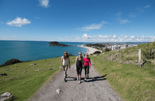 Girls walking up the gravel track, green on either side, blue ocean behind and blue skies
